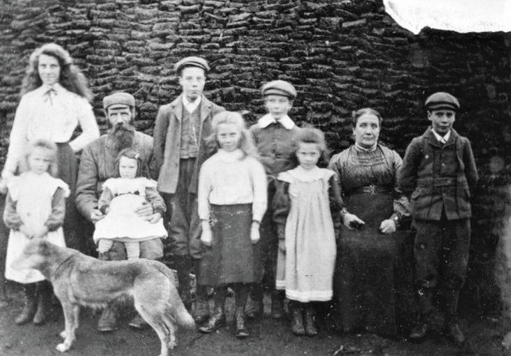 A family standing in front of their peat stack in West Helmsdale, c.1910.